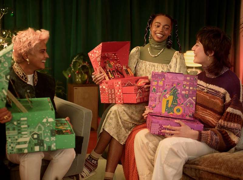 Three people opening their advent calendars
