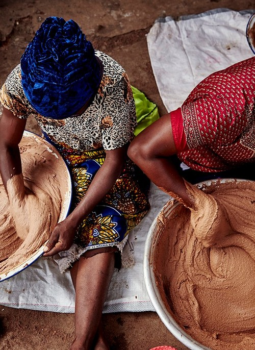 Two women mixing shea butter
