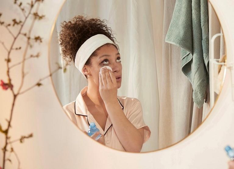 Reflejo de una mujer en un espejo desmaquillándose los ojos