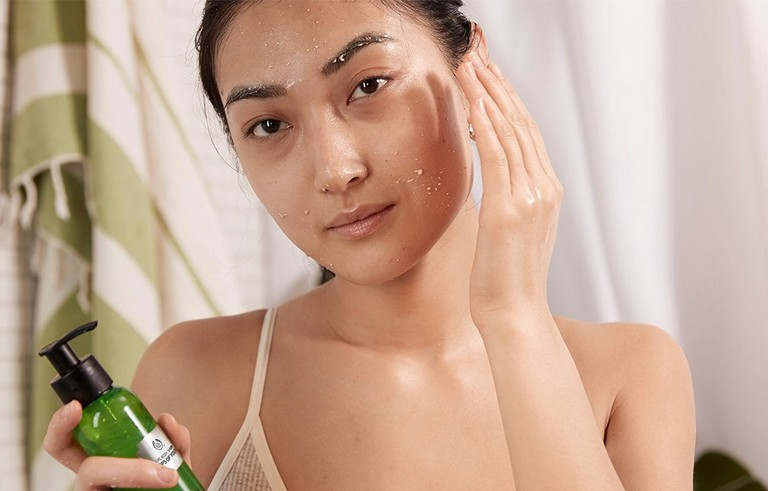 Model holding Drops of Youth Peel Off Mask and applying to face