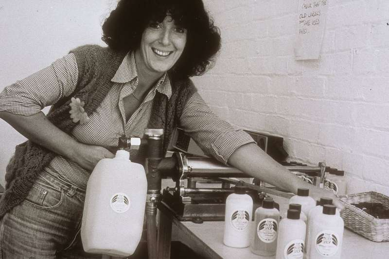 Black and white photo of woman stood holding bottles of beauty product