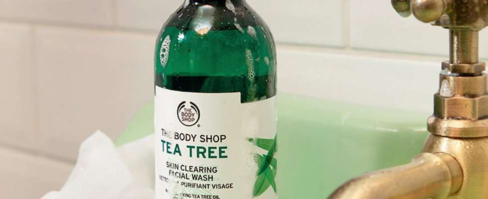 Tea Tree Skin Clearing Facial Wash covered in soapy suds. The product is placed on a green bathroom sink in front of a white tiled backdrop