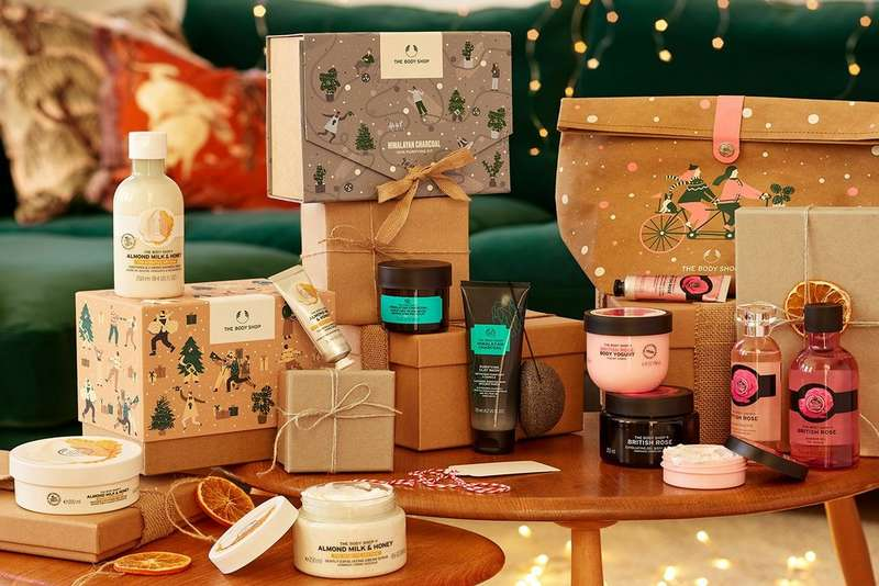 Selection of The Body Shop Christmas gift sets on a wooden table, surrounded by recycled wrapping paper and handmade decorations.