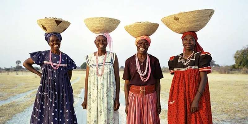 Women standing in row with baskets on head