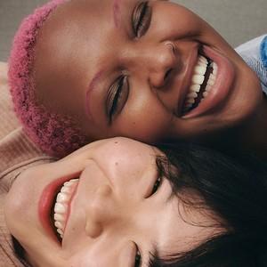 Dos mujeres sonriendo con las caras juntas