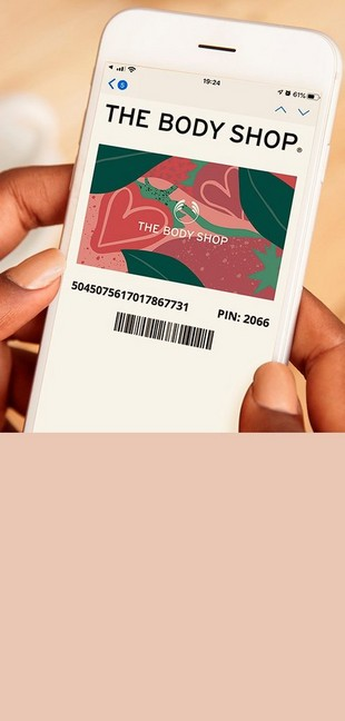 Woman holding phone. On the screen there is a pink floral The Body Shop gift card.