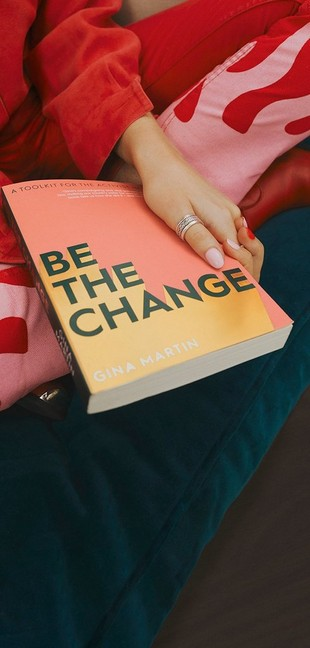 Woman holding a book that reads 'be the change' on the front
