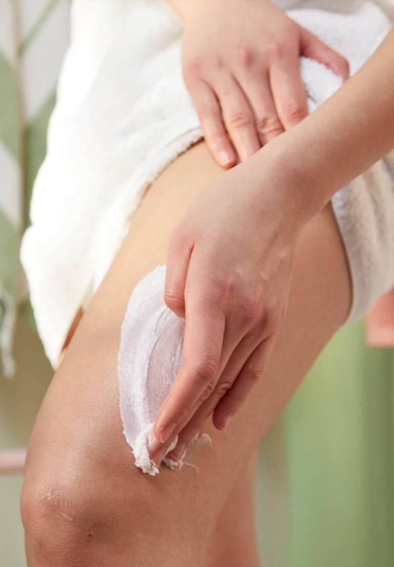 Woman applying moisturiser to legs