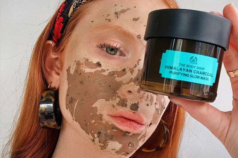 Woman wearing Himalayan Charcoal Mask whilst holding the product next to her face