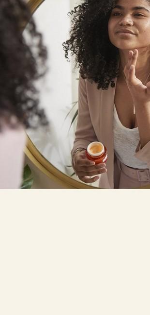 Mujer aplicando crema crema en el rostro mirándose en el espejo