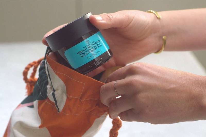 Model placing a face mask into a bespoke gift bag