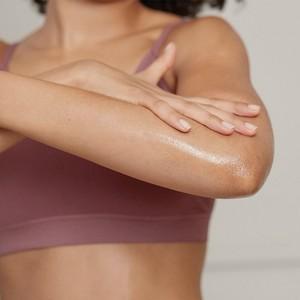 Model, das Creme in ihren Arm einreibt