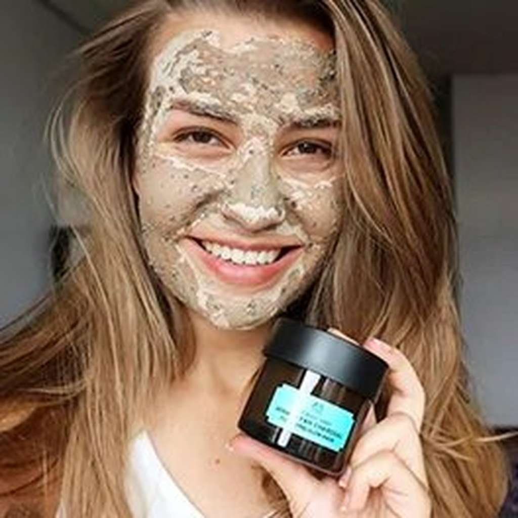 LADY WITH FACE MASK HOLDING HIMALAYAN CHARCOAL PURIFYING CLOW MASK POT