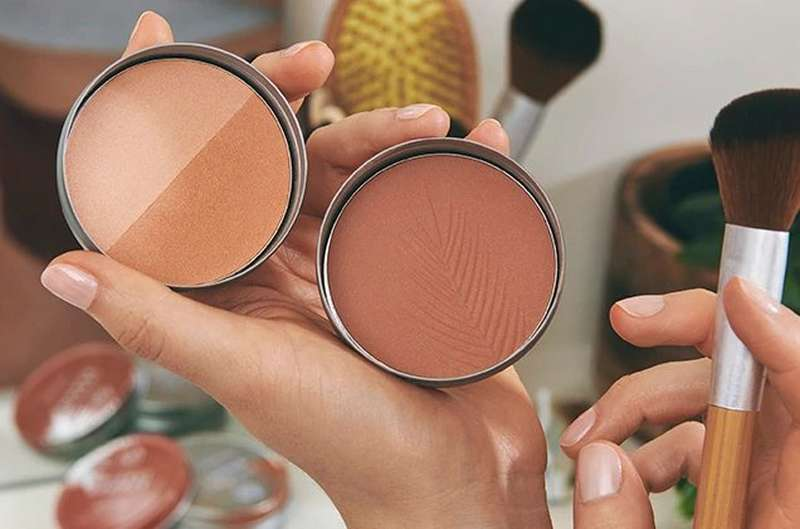 HAND HOLDING BRONZER AND BRUSHES