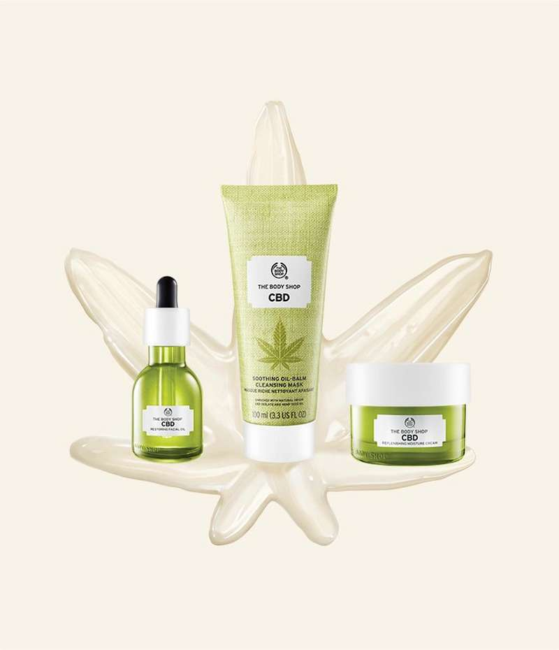 CBD facial oil and cleansing mask against a cream backdrop with a skincare product painted in the shape of a CBD leaf