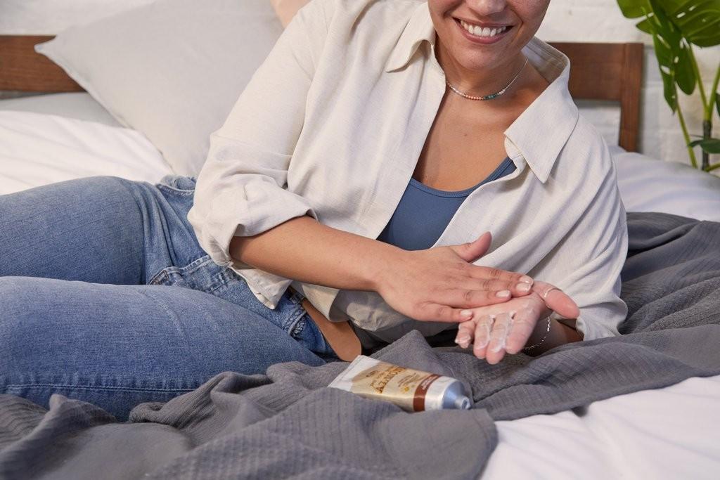 WOMEN RUBBING CREAM INTO HANDS