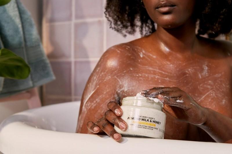 Une femme applique le gommage à l'amande et au miel de The Body Shop