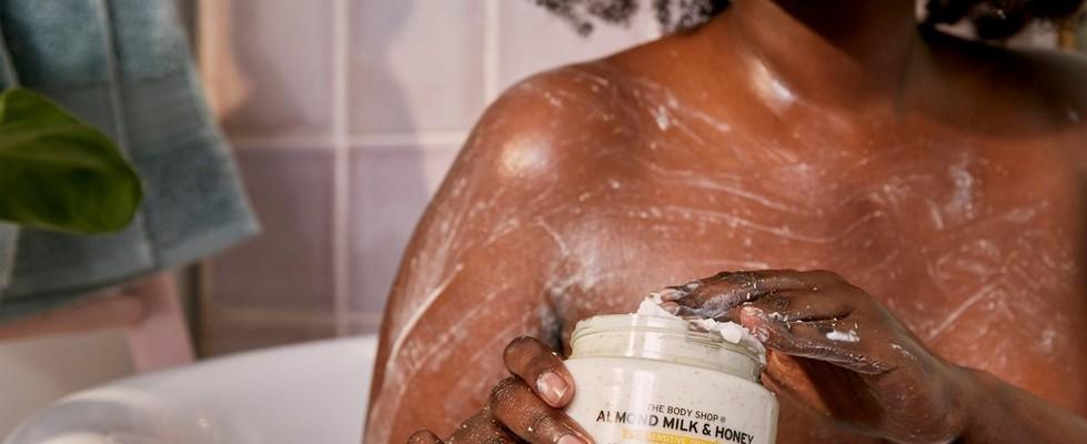 Woman applying exfoliating cream scrub in the bath