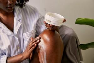 Woman in a bath applying moisturizer