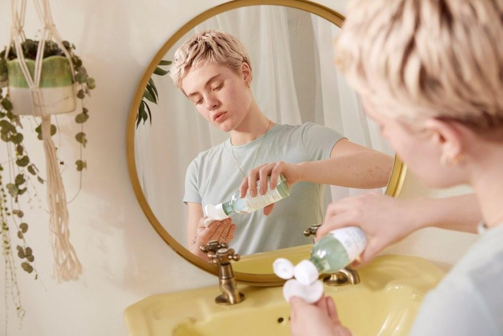 Frau bei der Verwendung von Gesichtswasser