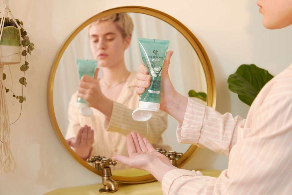 Woman squeezing Aloe soothing gel into her hands