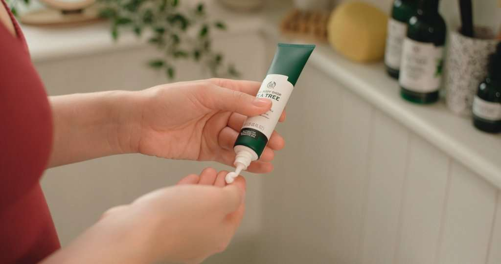 Hands squeezing face moisturiser from tube