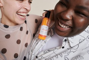 Ladies laughing with The Body Shop Vitamin C product