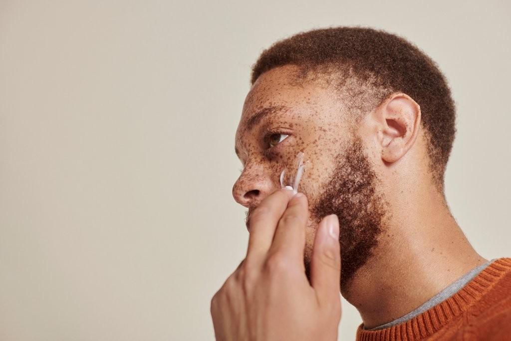 Un hombre se aplica crema facial