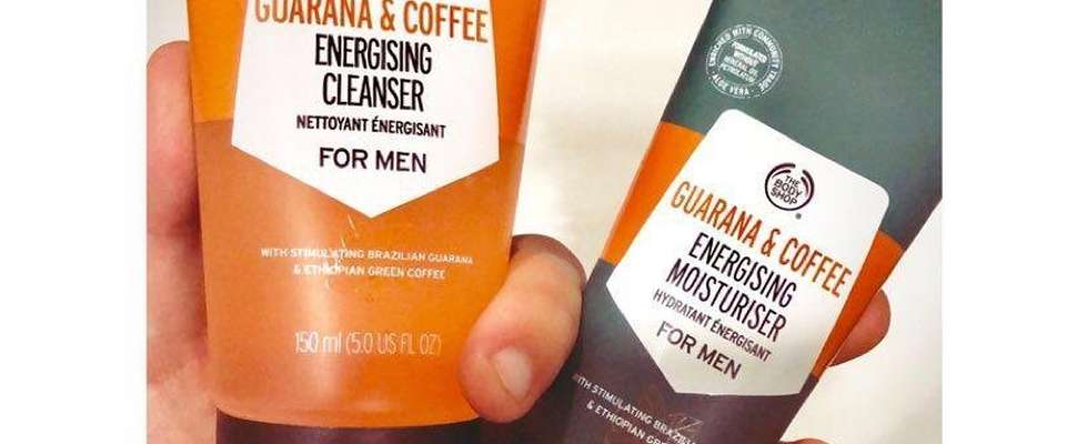 Hand holding The Body Shop Guarana & Coffee Energising Cleanser and Moisturiser