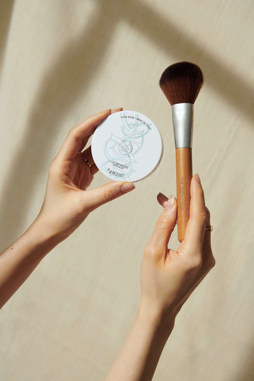 Hands holding The Body Shop Face Base and makeup brush