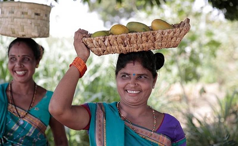Vrouwen die manden met fruit op hun hoofd dragen