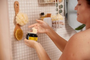 Woman scooping The Body Shop Banana Hair Mask