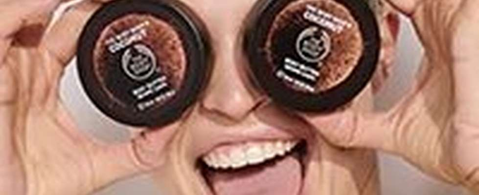 WOMEN HOLDING BODY SHOP POTS OVER HER EYES LAUGHING