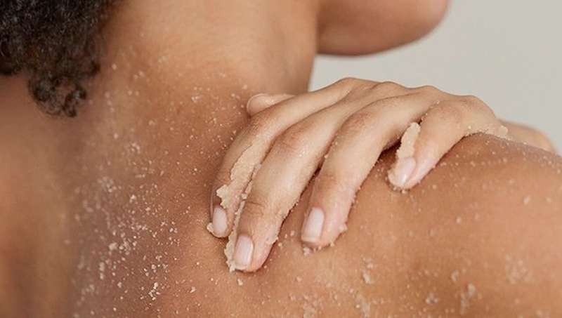 Woman applying exfoliating cream to shoulder