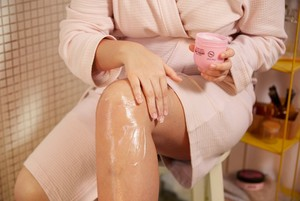 Woman applying The Body Shop Body Yoghurt to her legs