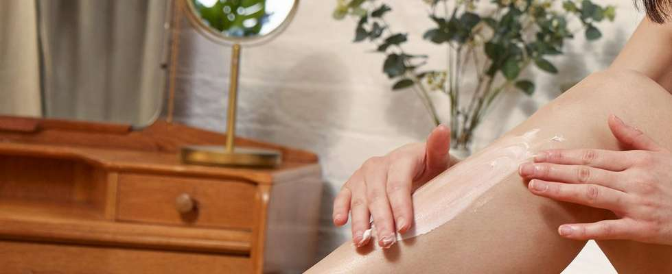 一位正在腳上塗抹身體潤膚霜的女士