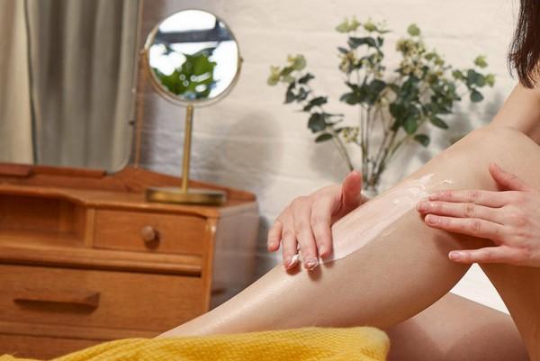 Woman rubbing cream on her leg