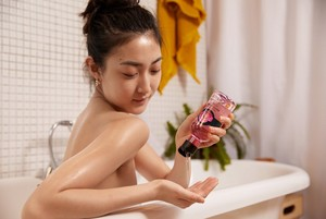 Woman in bath using The Body Shop British Rose Shower Gel
