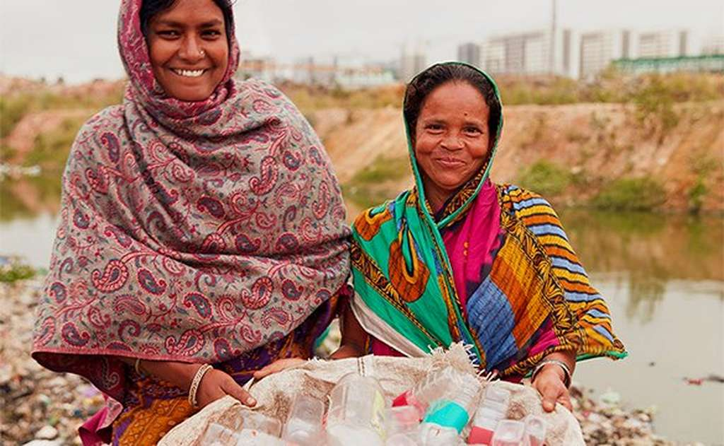 Two women holding basket of plastic bottles