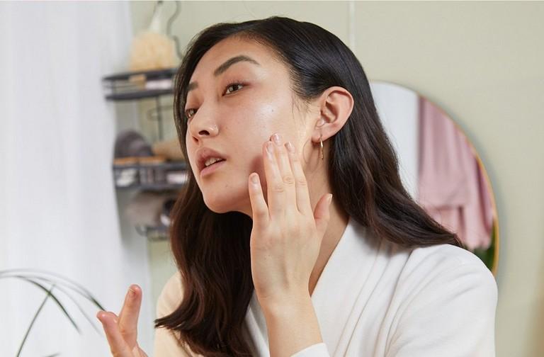 mujer aplicando un producto de cuidado facial en el rostro