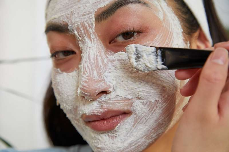 Woman applying face polishing mask
