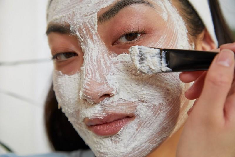 Frau beim Auftragen von Gesichtsmaske für strahlende Haut