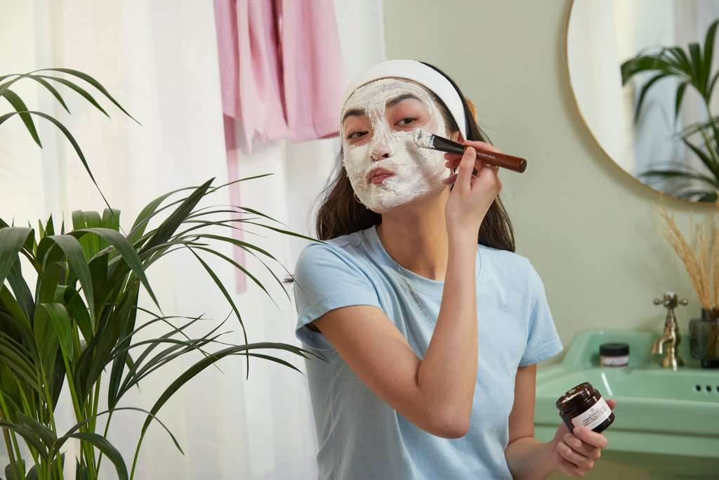 Woman applying polishing face mask