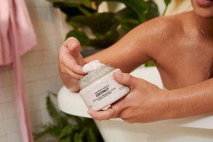 Hands scooping The Body Shop Coconut Exfoliating Body Cream