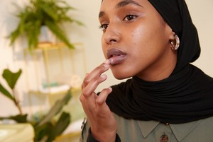 Image of woman applying lip butter