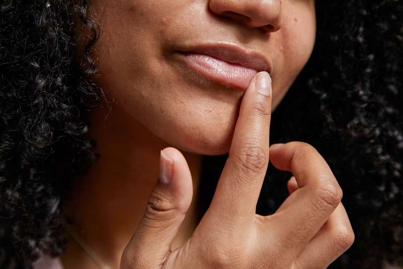 Woman touching her lip with her finger