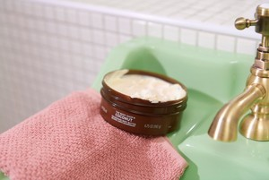 Burk med Body Shop Coconut Body Butter på ett handfat