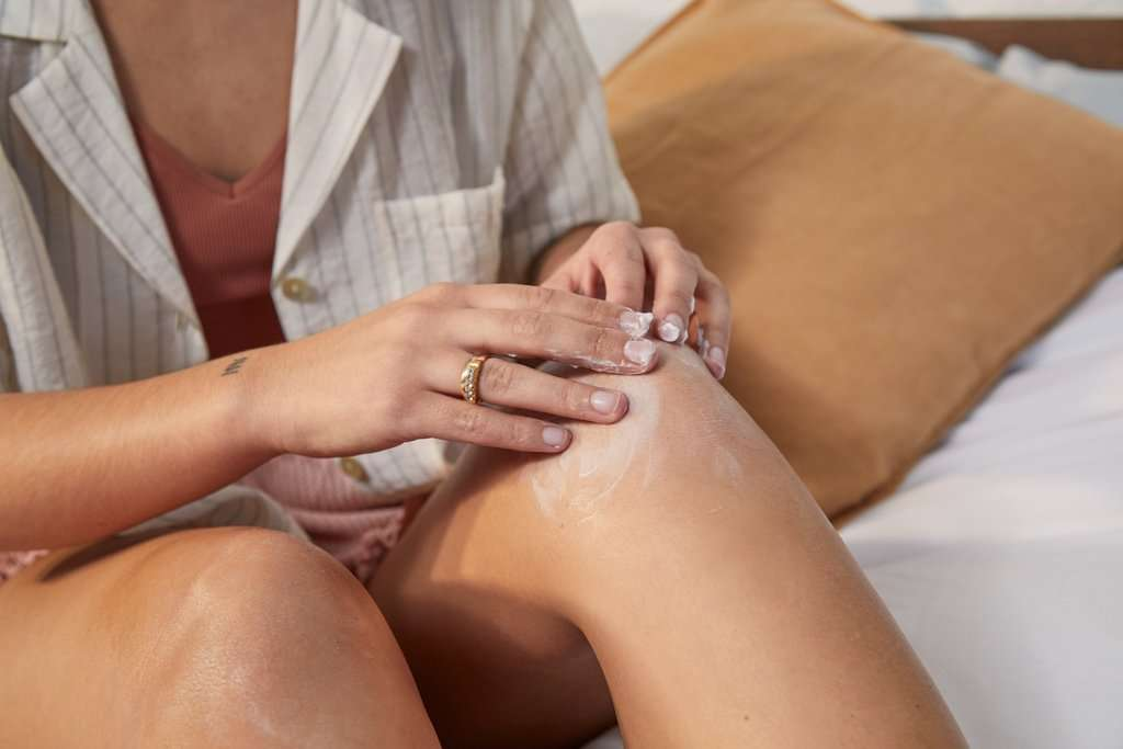 Woman applying body butter to her leg