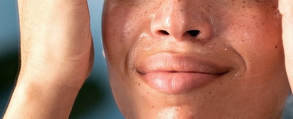 Model applying skincare to face