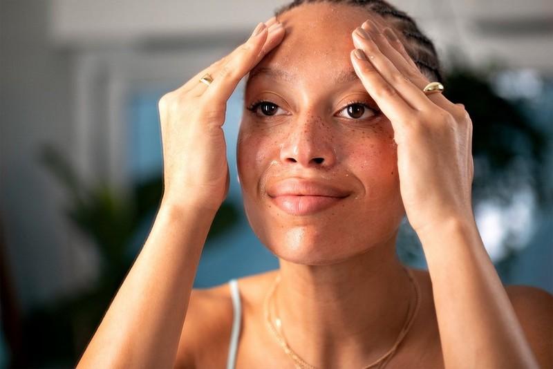 Frau, die Creme in ihre Stirn einreibt
